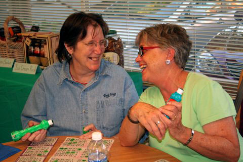 Two women laugh while playing bingo.