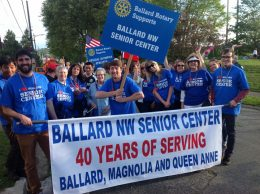Ballard Rotary supports the Ballard NW Senior Center. Group of people holding banner as if in a parade.